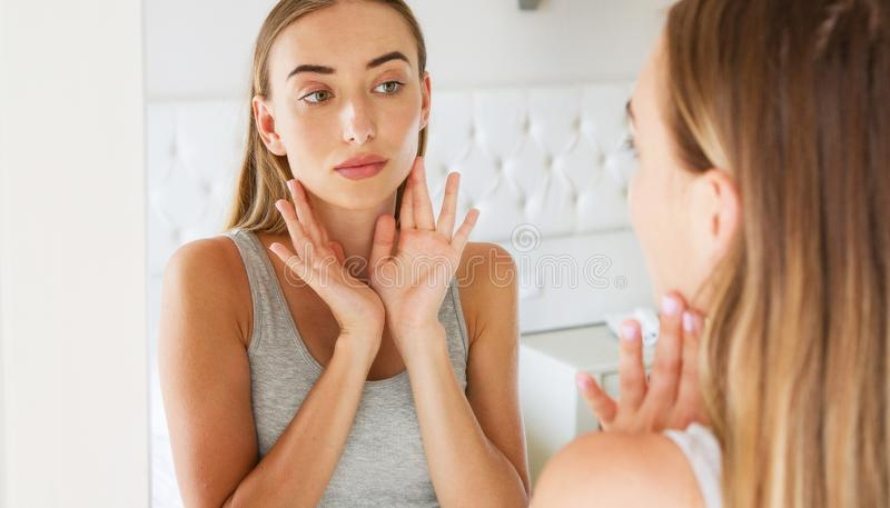 Unhappy girl in front of a mirror looking at her wrinkles.  royalty free stock images