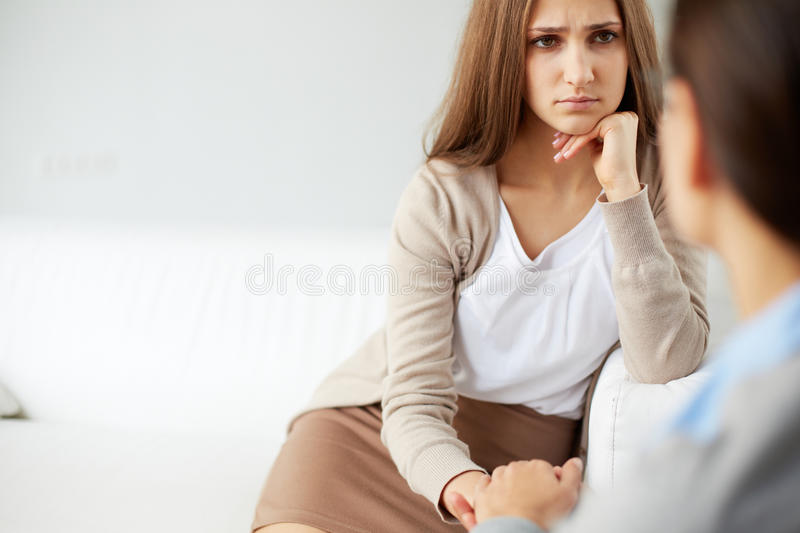 Unhappy girl. Image of sad patient looking at psychiatrist during discussion of her problem royalty free stock photography