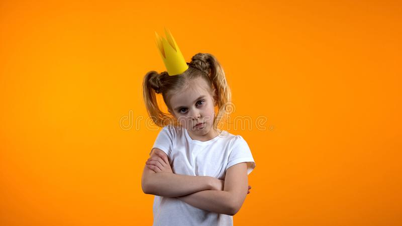 Unhappy girl in paper princess crown looking to cam with hands crossed on chest royalty free stock photography