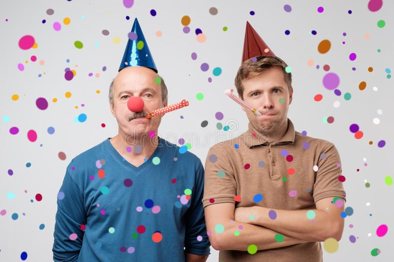 Unhappy guys are on party. Son and father are upset and do not want to have fun. royalty free stock photography