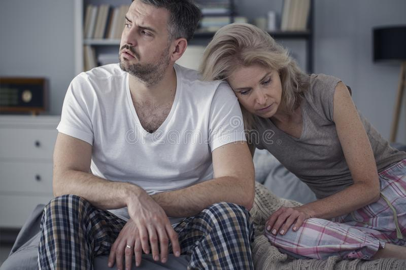 Unhappy husband and sad wife. Sitting together in the bedroom. Difficult marriage concept royalty free stock images