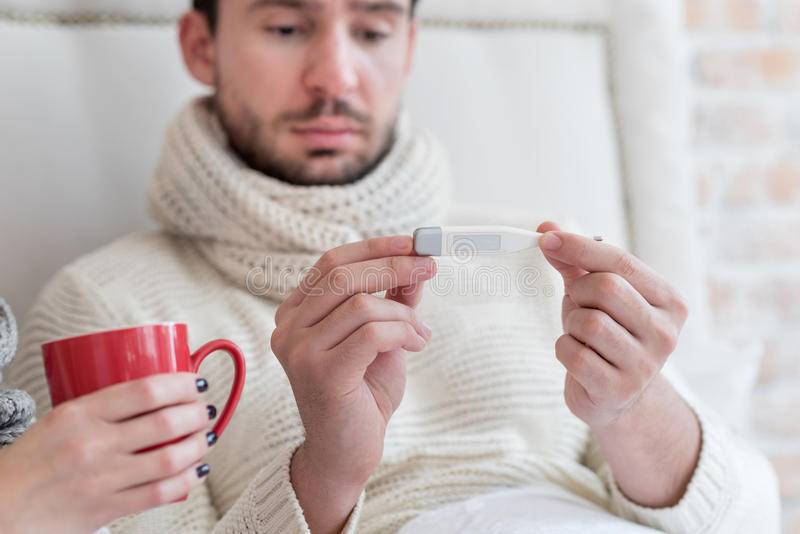 Unhappy ill man having a fever royalty free stock images