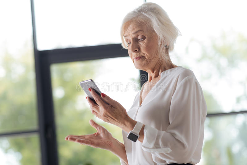 Unhappy irritated woman looking at her phone royalty free stock photography