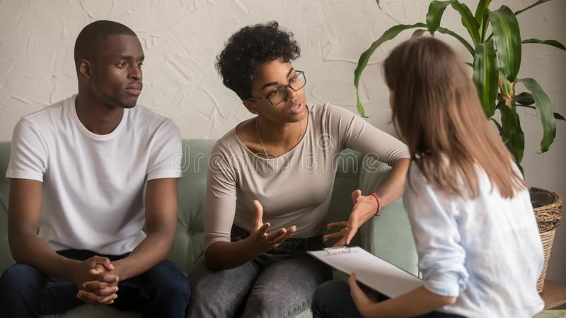 Unhappy african wife talking to psychologist complaining on bad relationship stock photos