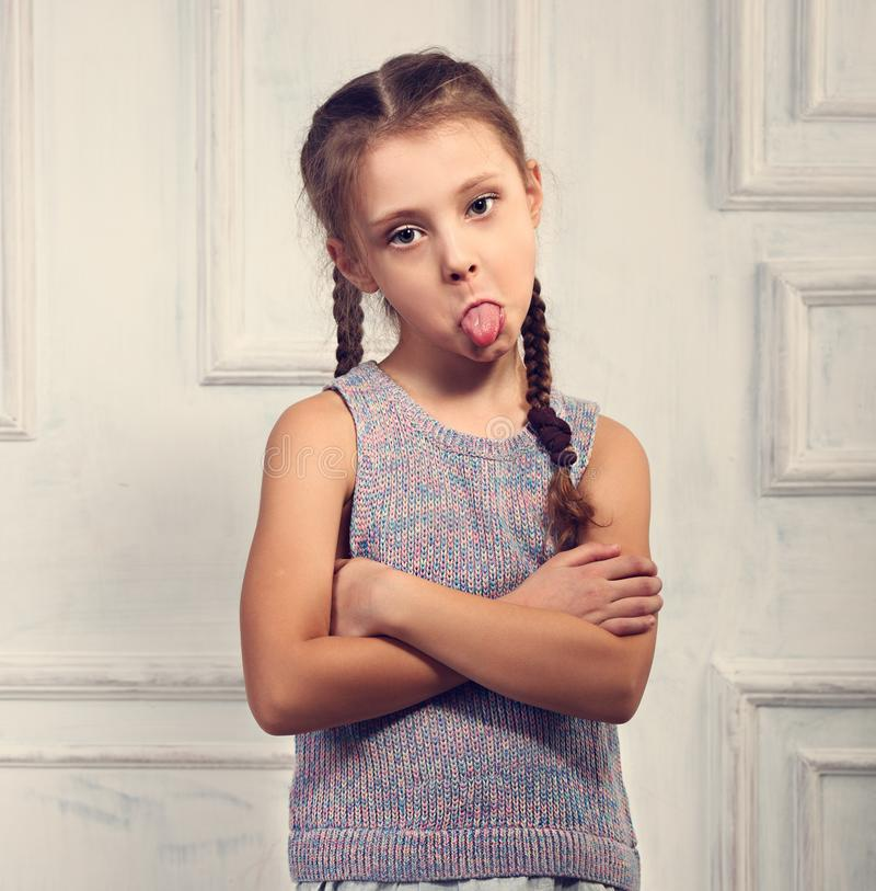 Unhappy kid girl in stylish clothing looking and showing the ton. Gue with folded arms on studio wall background. Toned closeup portrait stock images