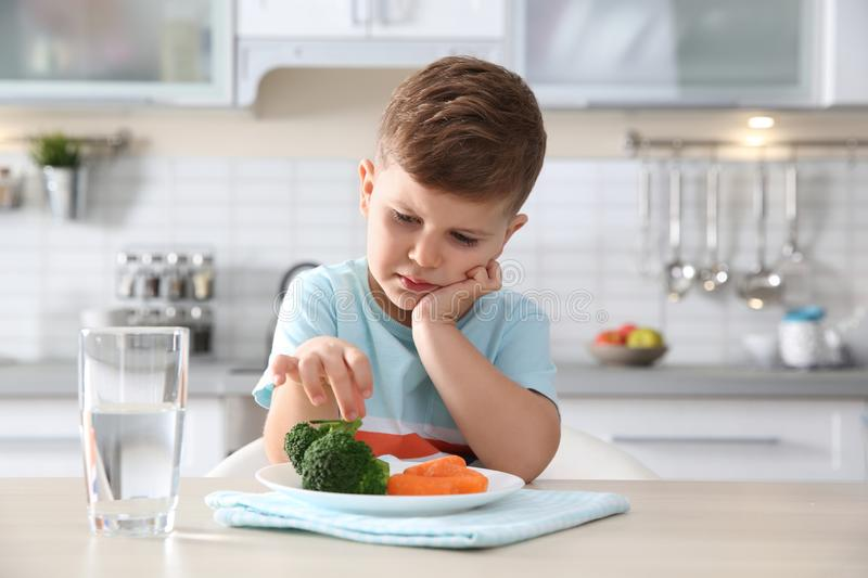 Unhappy little boy eating vegetables at table stock photos