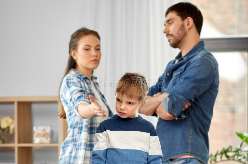 Unhappy little boy over arguing parents at home stock image