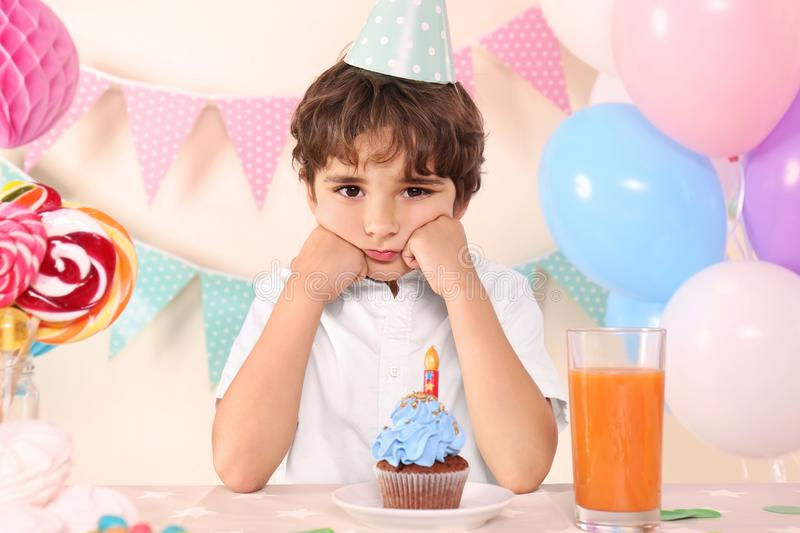 Unhappy little boy with party hat and cupcake on his birthday at home royalty free stock image
