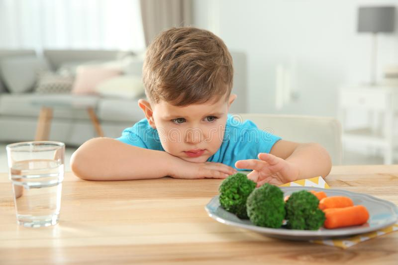 Unhappy little boy refusing to eat vegetables at table stock photo