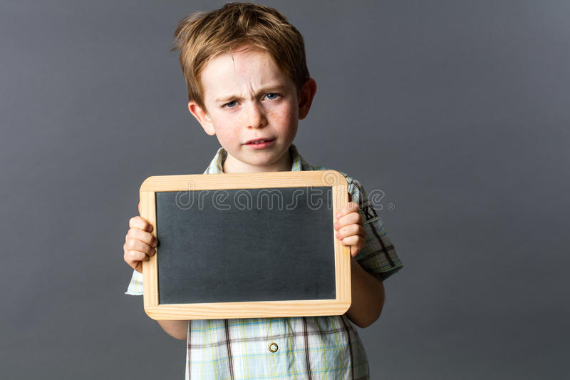 Unhappy little child showing empty writing slate to express reflection stock photo