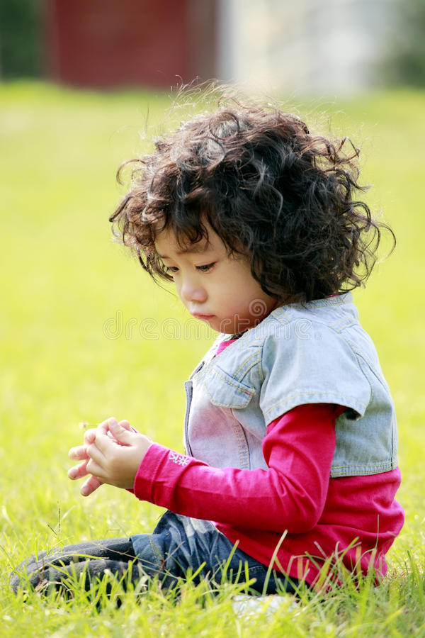 Unhappy Little Girl On The Grass Stock Photo