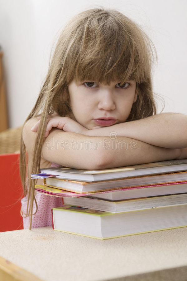 Unhappy Little Girl Sitting At The Desk Royalty Free Stock Photography