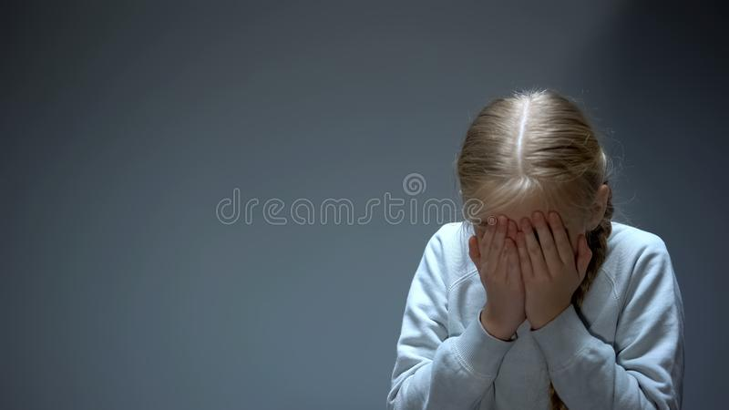 Unhappy little kid closing eyes with hands, bullying and family violence victim stock images