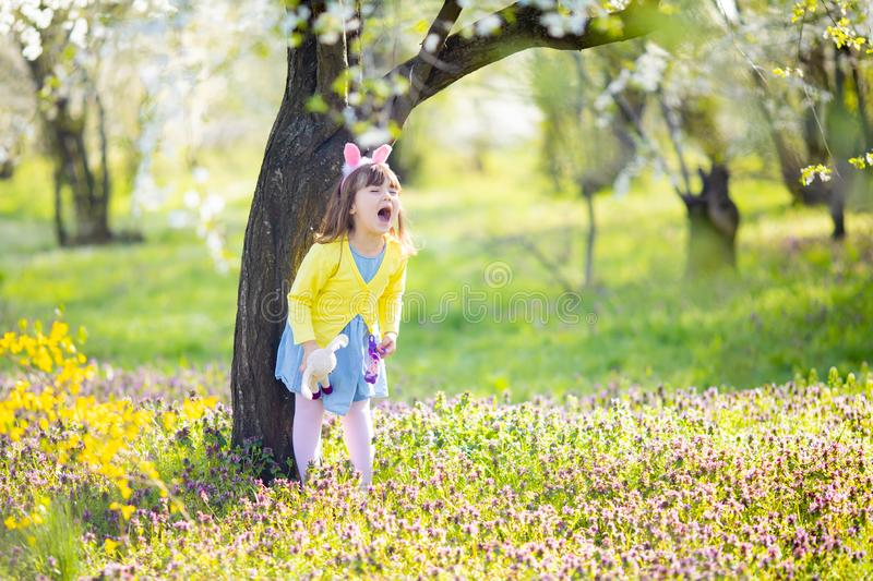 Unhappy little sad and angry crying bunny girl holding rabbit toy in the spring blossom garden stock image