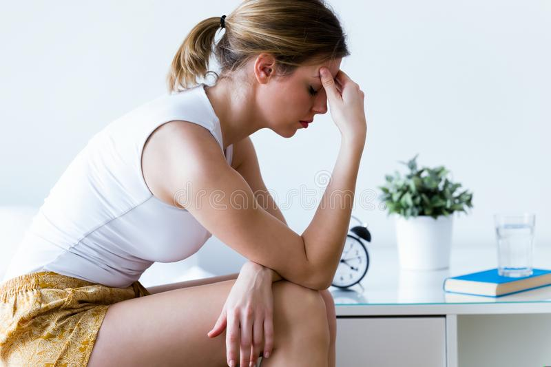 Unhappy lonely depressed young woman sitting on bed at home. Depression concept. stock photography