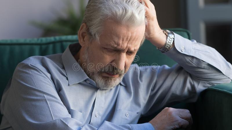 Unhappy lonely grey haired mature man sitting alone horizontal banner. Unhappy lonely grey haired mature man sitting alone, sad old husband missing wife, upset stock photography