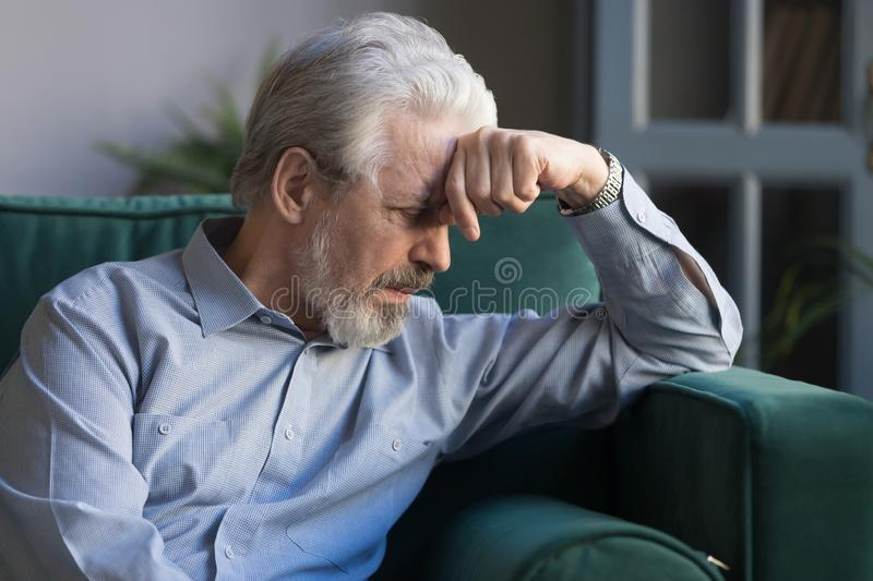 Unhappy lonely grey haired mature man sitting on couch. Alone, holding head on hand, sad old husband missing wife, upset middle aged male lost in thoughts stock photo