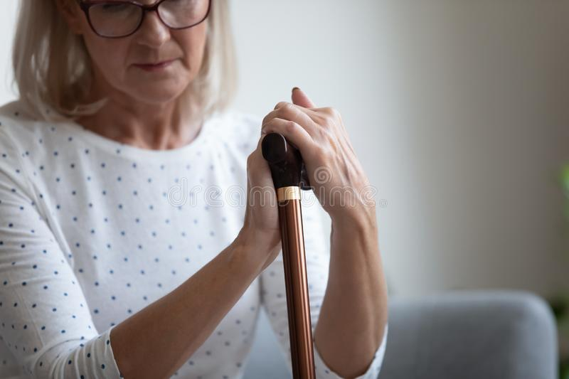 Unhappy lonely mature woman holding walking stick close up stock photos