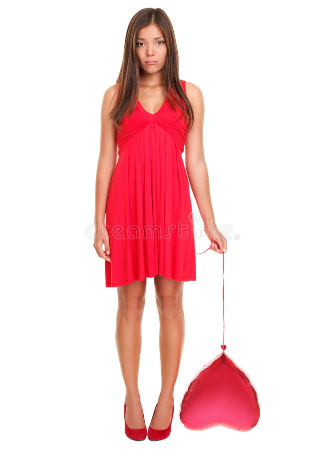 Unhappy love - funny valentines day woman. Sad woman in love ? funny. Valentines day woman unhappy holding red heart balloon Beautiful young woman in red dress royalty free stock photo