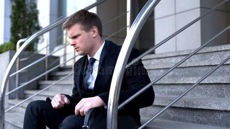 Unhappy male company manager sitting outside office building, dismissal despair stock photos