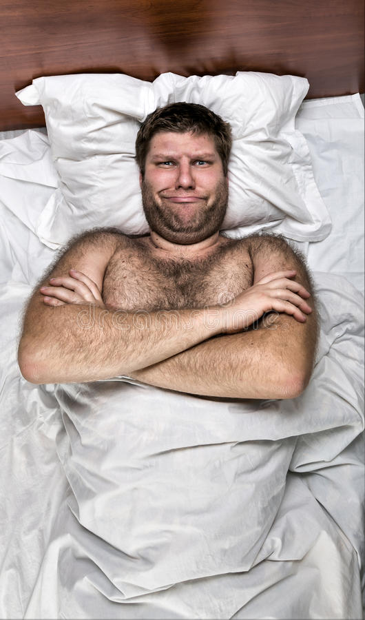 Unhappy man in bed with crossed hands stock images