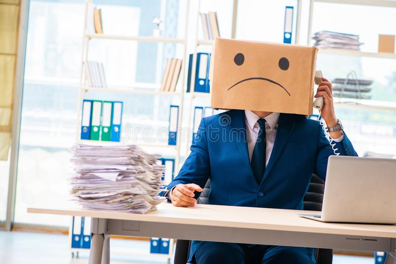 The unhappy man with box instead of his head royalty free stock image