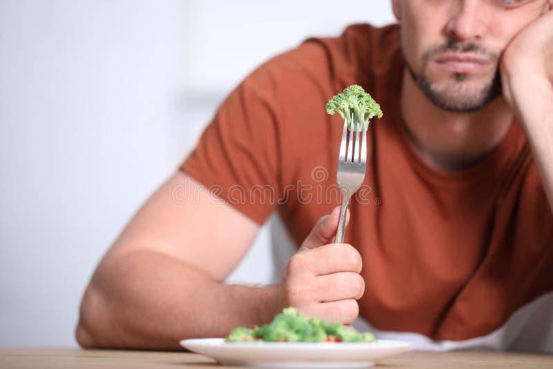 Unhappy man with broccoli on fork at table. Closeup stock photos