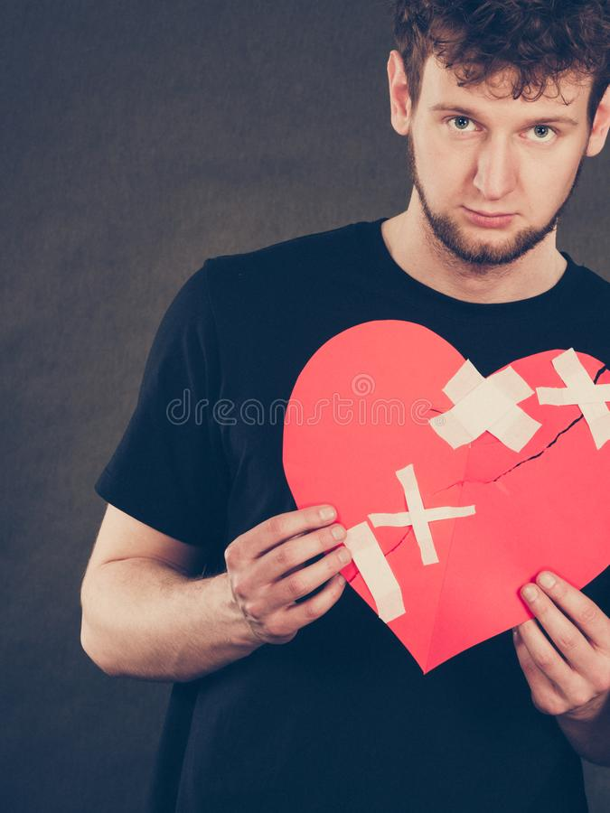 Unhappy man with broken heart. Separation and conflict. Young upset sad man with red heart glued by plaster. Guy lost his love relationship. Valentines Day royalty free stock photos