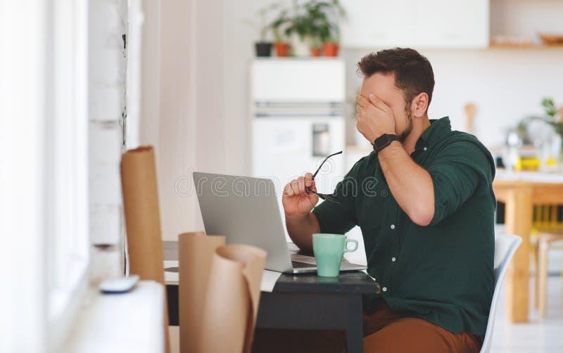 Unhappy man businessman, freelancer, student working at computer stock photos