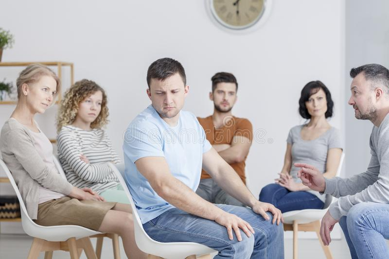 Unhappy man during group therapy. Unhappy men during AA group therapy with caucasian people stock photography