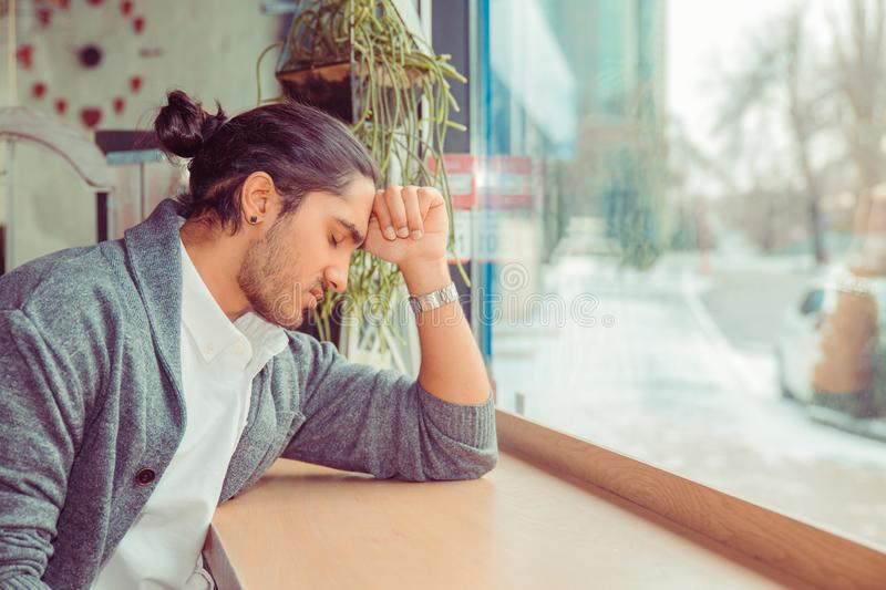 Unhappy man holding his forehead with hand while having headache or depression royalty free stock photos