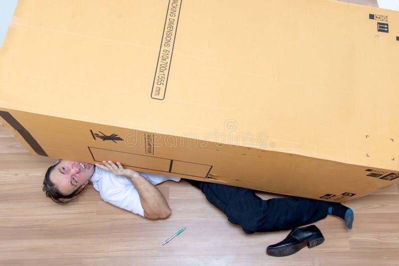 The unhappy man lying under a big box. royalty free stock photos