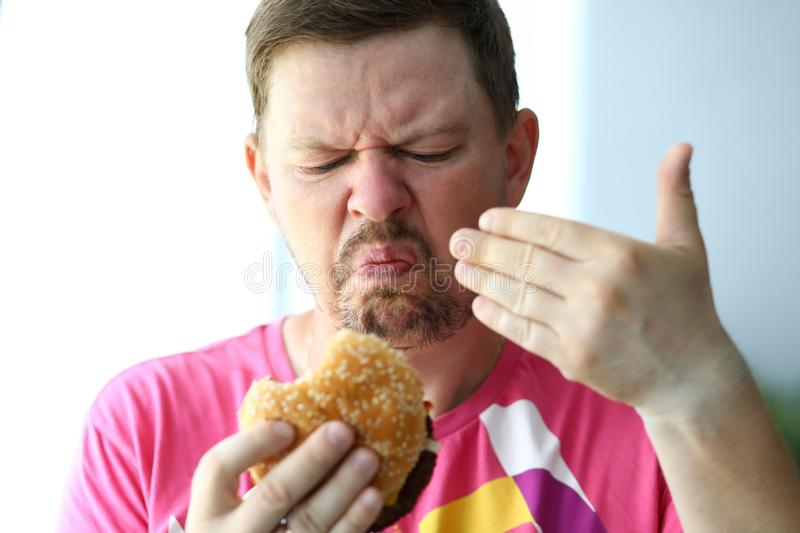 Unhappy man sniffing suspicious burger examining its freshness royalty free stock photography