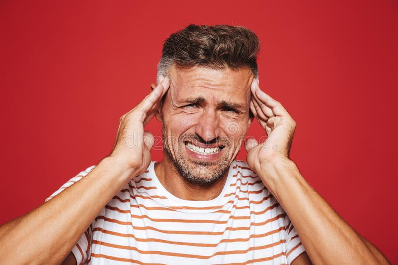 Unhappy man in striped t-shirt screaming and rubbing temples bec. Ause of headache isolated over red background stock photos