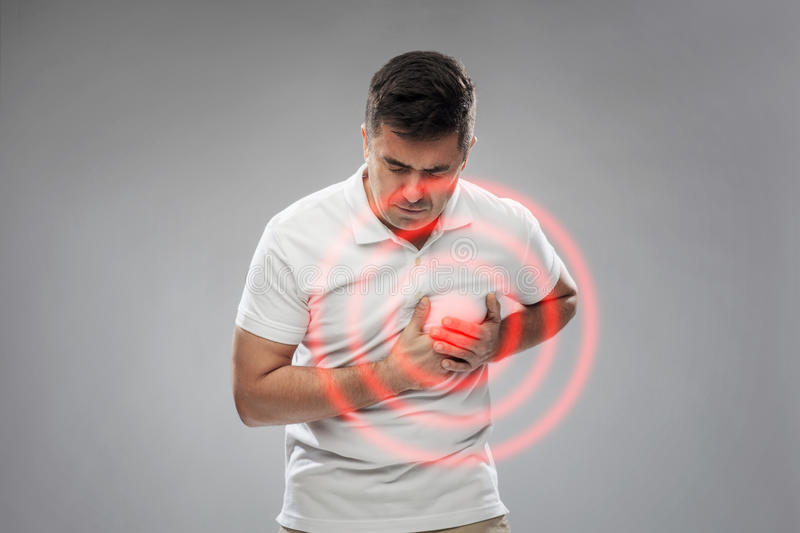 Unhappy man suffering from heart ache. People, healthcare and problem concept - unhappy man suffering from heart ache over gray background stock photography