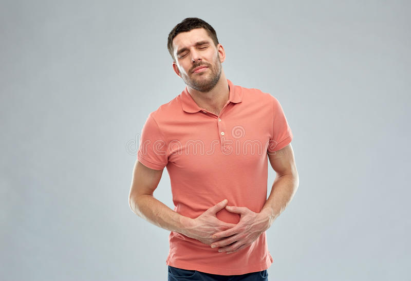 Unhappy man suffering from stomach ache. People, healthcare and problem concept - unhappy man suffering from stomach ache over gray background stock photos