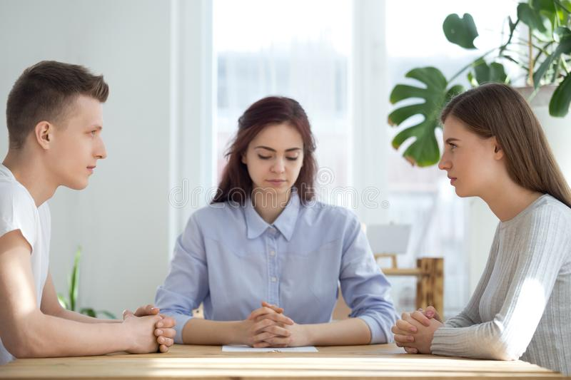 Unhappy married couple sitting opposite getting divorced in lawyer office. Unhappy young married couple sitting opposite getting divorced in lawyer office before stock images