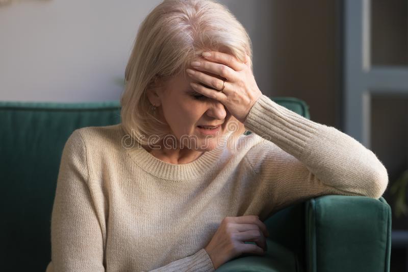 Unhappy mature grey haired woman suffering from headache close up stock photography