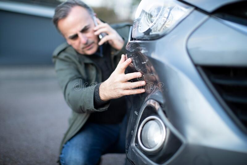 Unhappy Mature  Male Driver With Damaged Car After Accident Calling Insurance Company On Mobile Phone stock photos