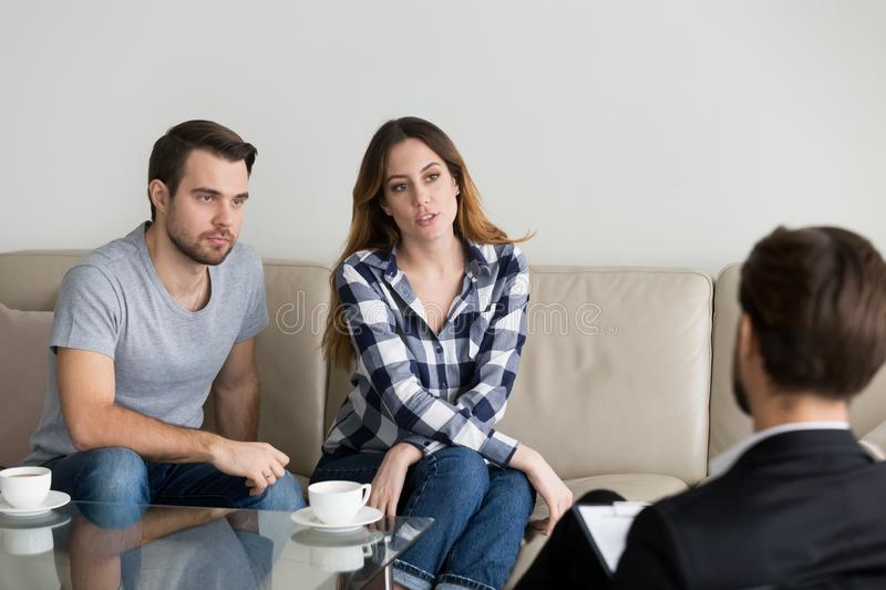 Unhappy millennial couple talking to psychologist sitting on couch. Visiting counselor sharing problems in bad relationships at family therapy session, marriage stock photography