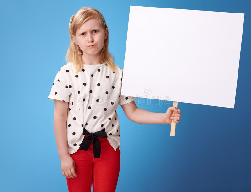 Unhappy modern girl in red pants on blue showing blank poster. Unhappy modern girl in red pants showing blank poster against blue background stock photos