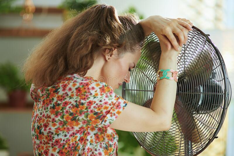 Unhappy modern middle aged woman suffering from summer heat royalty free stock photo