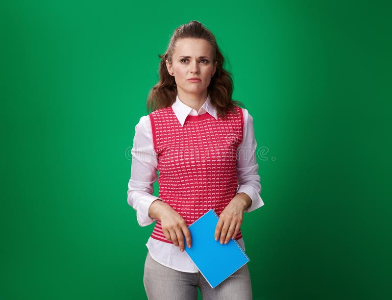 Unhappy student woman with blue notebook isolated on green royalty free stock photos
