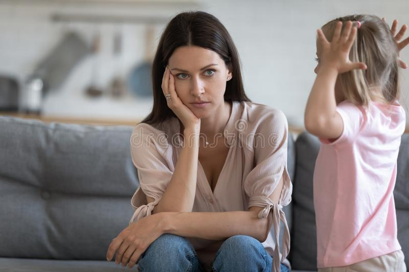Unhappy mother having problem with noisy naughty little daughter stock images