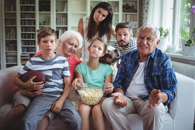 Unhappy multi-generation family watching soccer match on television in living room stock image