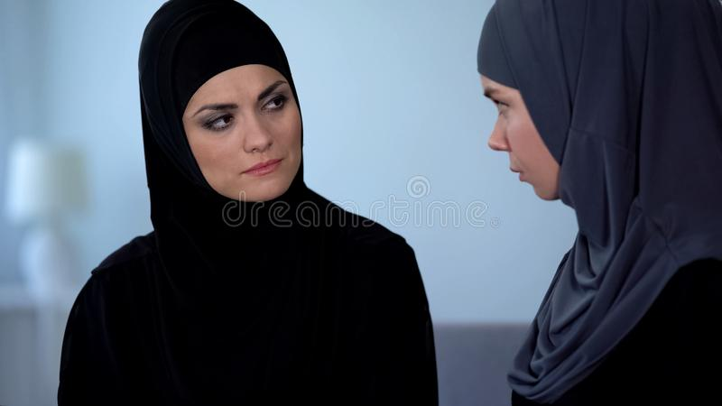 Unhappy muslim wife listening and sadly looking at friend, islamic obedience. Stock photo stock photo