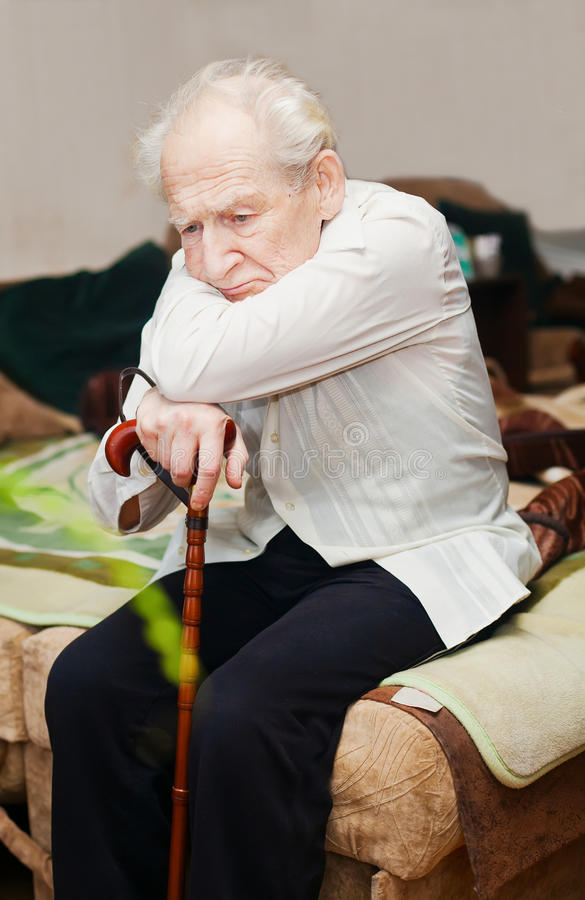 Unhappy Old Man With Cane. Sad lonely old man sitting with his cane royalty free stock image
