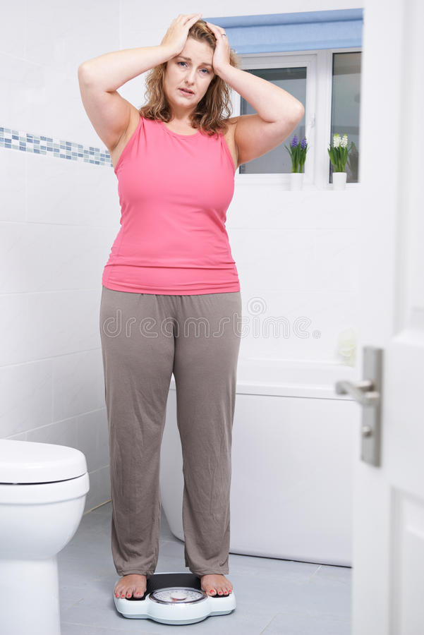 Unhappy Overweight Woman Weighing Herself On Scales In Bathroom stock photos