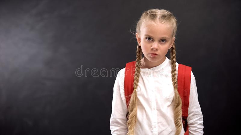 Unhappy pupil looking at camera, hating unloved school, problem child concept. Stock photo stock photo