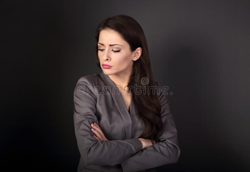 Unhappy resentful business woman in suit with folded arms looking down on dark grey background stock photos
